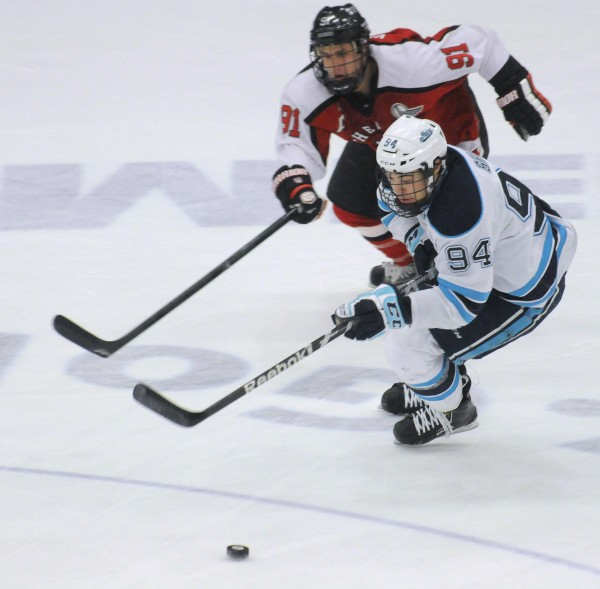 The University of Maine's Devin Shore (right) and Northeastern's Robbie Vrolyk battle for the puck during the first period of the game in Orono.