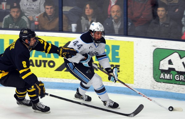 Merrimack's Brian Christie (left) defends as Maine's Conor Riley attempts a shot at the goal in the first period of their game Friday night, Jan. 18, 2013, at Alfornd Arena.