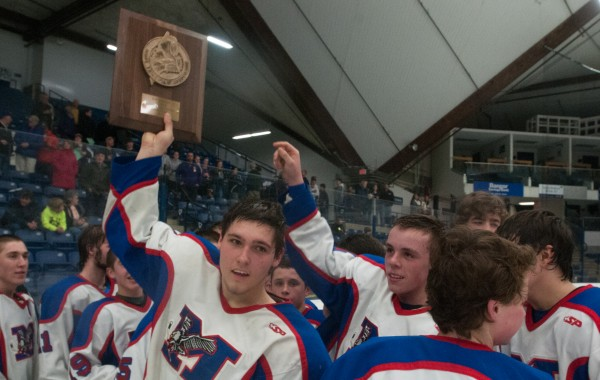 Messalonskee defenseman Kalib Bernatchez holds up the Eastern Maine Class B championship plaque after defeating John Bapst at Alfond Arena at the University of Maine in Orono on Tuesday, March 5, 2013.