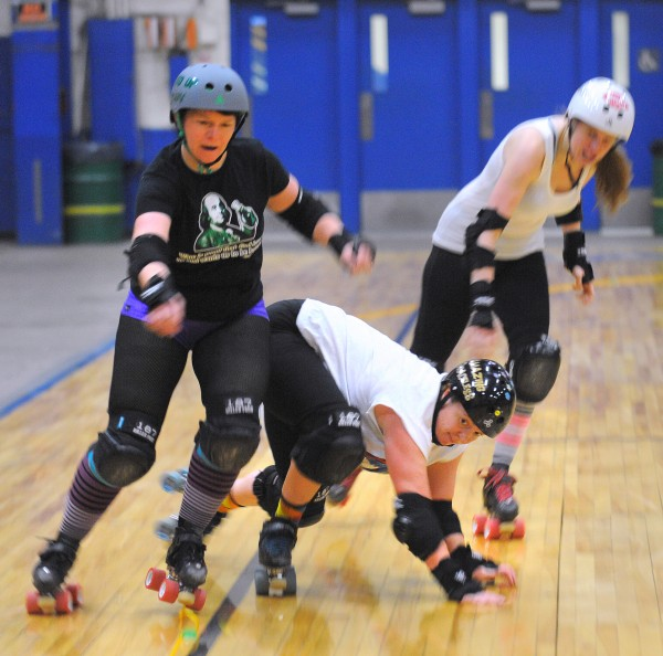Sara &quotAmazing Graceless&quot Miller (center) falls on the floor as she was trying to break the wall formed by Amy &quotWined Up&quot Blackstone (left) and Wendy &quotStargazer&quot Bingaman during the Central Maine Derby team's practice at the Bangor Auditorium Wednesday. The team will play against the Maine Roller Derby Riptide on Sunday at the Bangor Auditorium.