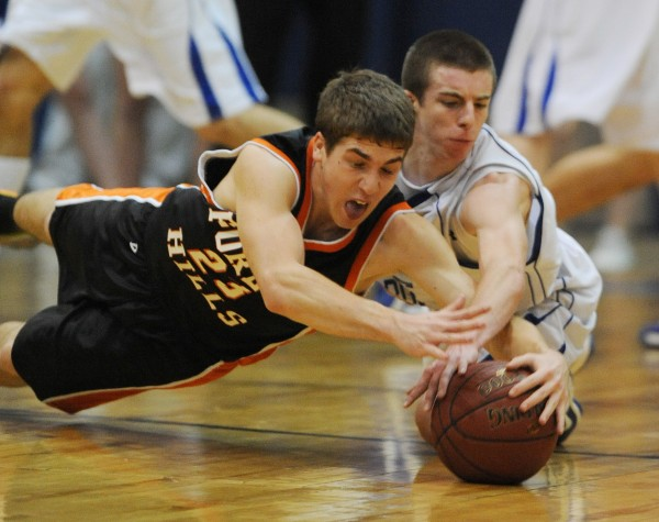Evan Worcester of Forest Hills and Central Aroostook's Chandler Brewer scramble for a loose ball during Class D state championship basketball action on Saturday at the Bangor Auditorium.