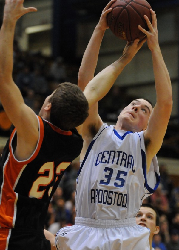 Central Aroostook's Spencer Garrison pulls down a rebound against Forest Hills' Evan Worcester during Class D state championship action on Saturday at the Bangor Auditorium.