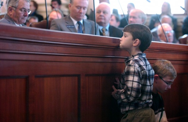 Benaiah Said, 7, peeks over the legislators' desk in the Maine House of Representatives chambers during the roll call before newly elected lawmakers took the oath of office on Wednesday morning, Dec. 6, 2006. Benaiah and his brother Jeremy, 10, (right) came to the ceremony with their mother, who works for one of the state representatives.