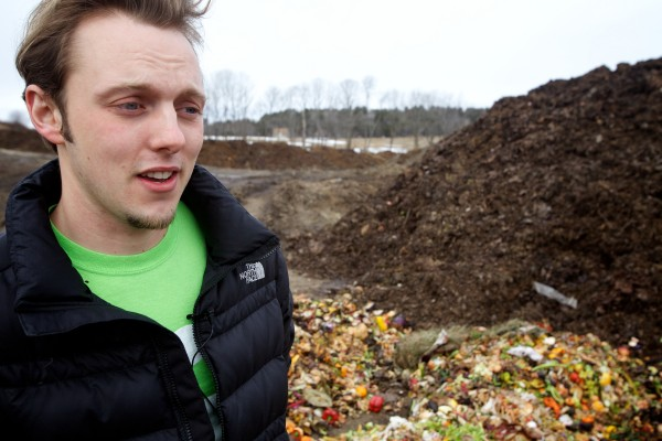 Tyler Franks of Garbage to Garden stands in front of a pile of composting food scraps at Eddie Benson's dairy farm in Gorham on Wednesday. Benson mixes the food scraps with sawdust and other materials to create certified organic compost.