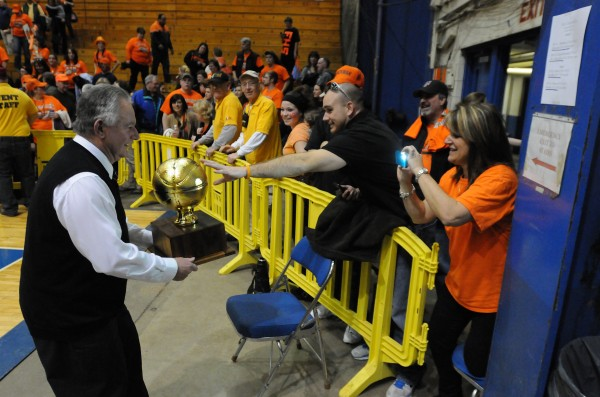 Assistant coach Bill Cost teases a fan with the Class D boys gold ball trophy after Forest Hills High defeated Central Aroostook 55-48 after the Class D state championship on Saturday at the Bangor Auditorium.
