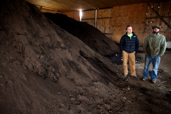 Tyler Frank (left) and Cory Fletcher of Garbage to Garden stand with some finished compost at Eddie Benson's dairy farm in Gorham on Wednesday. Frank and Fletcher collect food waste in the Portland area and Benson mixes it with sawdust and other materials to make certified organic compost.