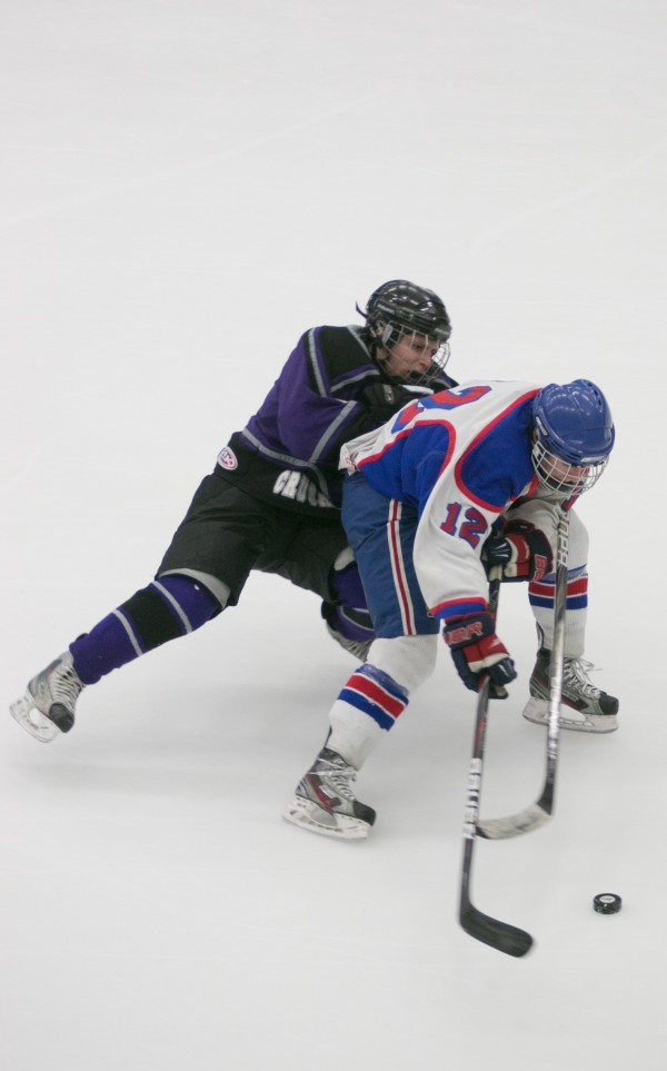 John Bapst defenseman Raymond Hummels (left) battles for the puck against Messalonskee forward Chase Cunnigman (right)during the Eastern Maine Class B championship game at Alfond Arena at the University of Maine on Tuesday, March 5, 2013.