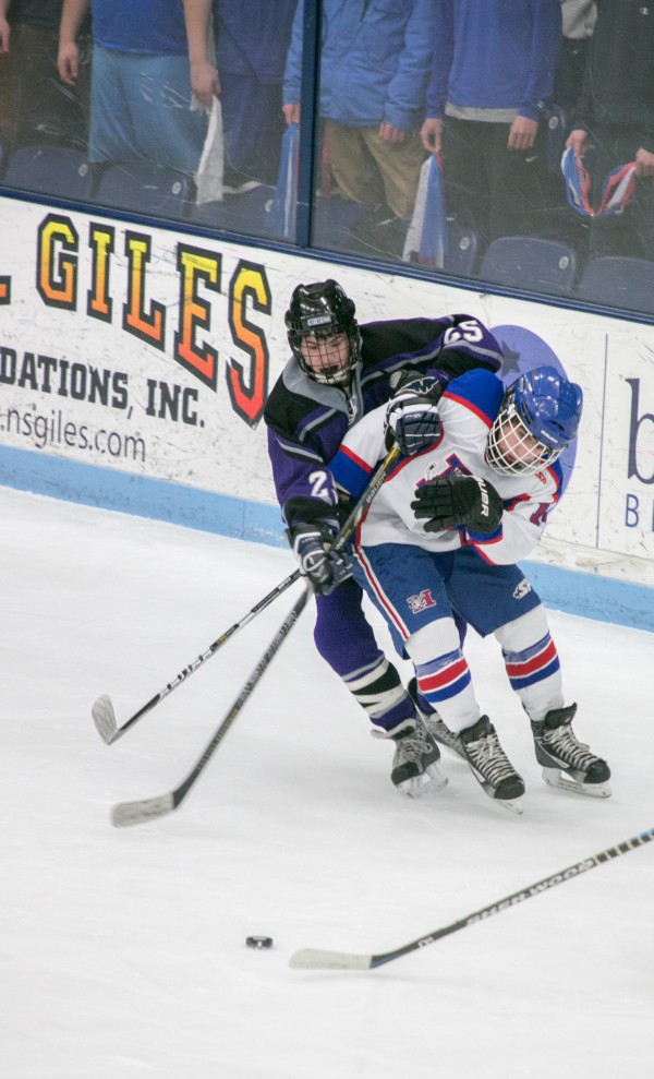 John Bapst forward Matthew Spear (left) and Messalonskee forward Devin Pickett (right) battle for the puck during the Eastern Maine Class B championship game at Alfond Arena at the University of Maine on Tuesday, March 5, 2013.