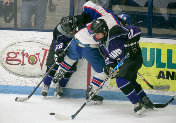 John Bapst forward Jonathan Cheff (right) grabs the loose puck after teammate Raymond Hummels (left) checks Messalonskee defenseman Kalib Bernatchez (center) during the Eastern Maine Class B championship game at Alfond Arena at the University of Maine on Tuesday, March 5, 2013.