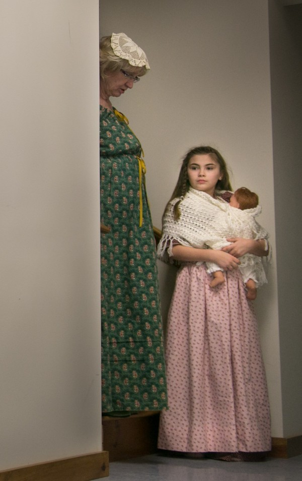 Judith Frost Gillis (left) and Isabella Gillis (right) wait in a hallway before their colonial reenactment for the Old Home Week announcement at the Orrington Meeting House on Thursday, March 21, 2013. Judith was portraying historic Orrington resident Azubah Freeman Ryder who, in 1814, at 9-months pregnant, ran door to door to alert local residents of British troops marching toward the town.