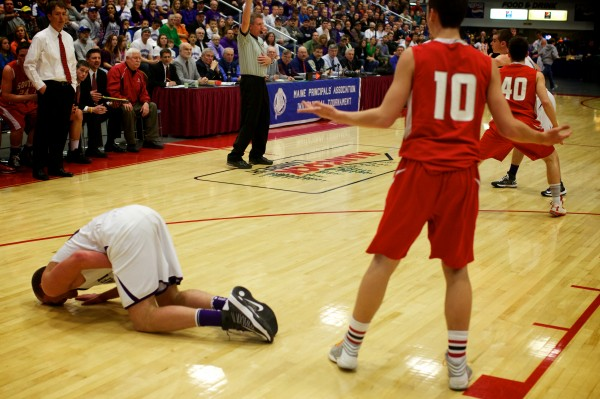 South Portland High School's Calvin Carr (left) pleads his innocence while a Hampden Academy player lies on the court Saturday at the Maine State Class A Basketball Championship game in Augusta.