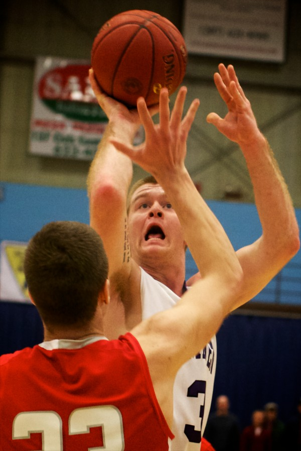 Hampden Academy senior forward Brian Fickett shoots over a defender from South Portland High School Saturday at the Maine State Class A Basketball Championship game in Augusta.