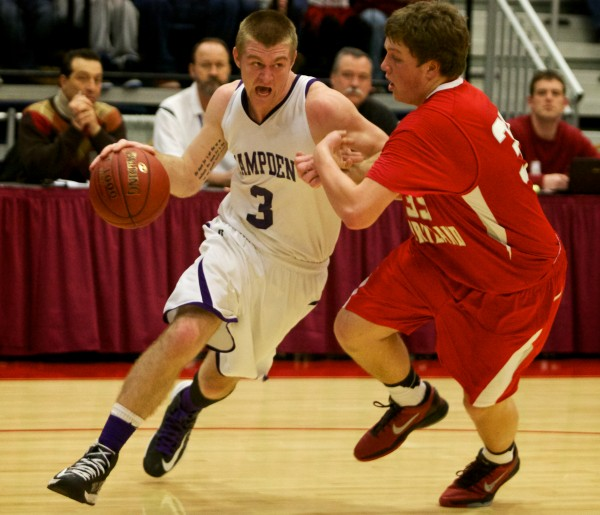 Brian Ficket of Hampden Academy drives around South Portland High School's Jaren Muller at the Maine State Class A Basketball Championship game Saturday in Augusta.