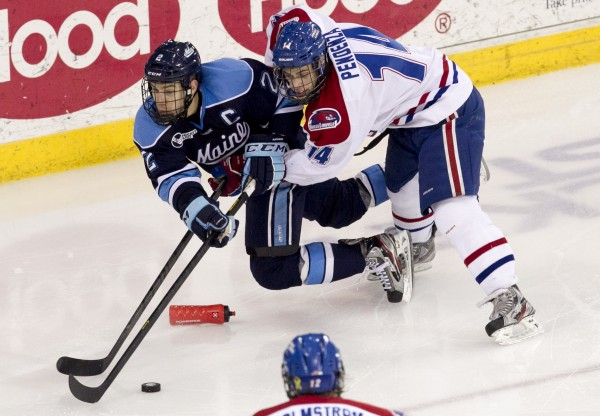 Maine's Stu Higgins (left) and UMass Lowell's Joseph Pendenza battle for the puck in the second period, Friday, March 15, 2013, in Lowell, Mass., during the second game of their Hockey East quarterfinal series.