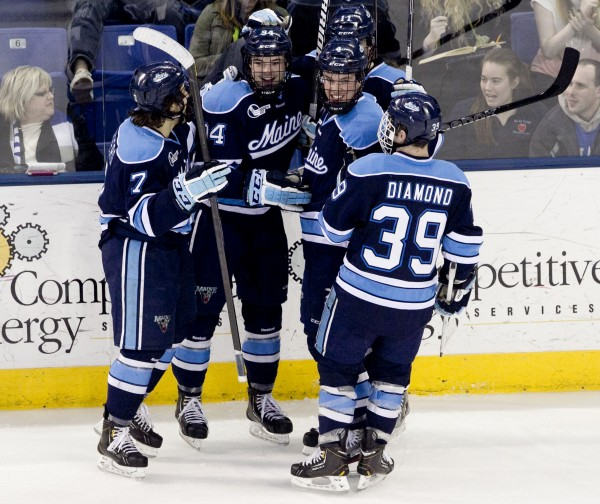 Ryan Lomberg (from left), Devin Shore, Steven Swavely and Joey Diamond celebrate Maine's first goal in the second period against UMass Lowell, Friday, March 15, 2013, in Lowell, Mass.,during the second game of their Hockey East quarterfinal series.