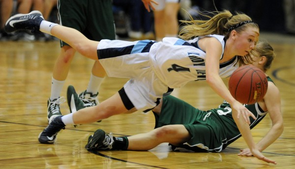 Calais guard Madison McVicar and Waynflete's Martha Veroneau get tripped up during the Class C girls state championship game at the Bangor Auditorium Saturday night.  Waynflete won the game 59-55.