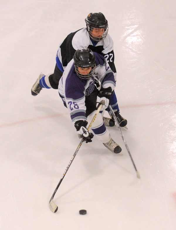 John Bapst's Ray Hummels (front) pushes the puck ahead of Houlton/Hodgdon's Brandon Malone during a game earlier this season. John Bapst will play for its first regional title when it takes on Messaonskee at 7 p.m. Tuesday in Orono.