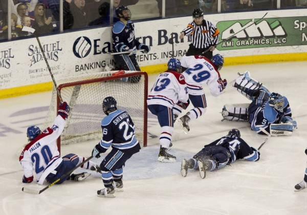 UMass Lowell's Derek Arnold scores the winning goal in overtime against Maine, Friday, March 15, 2013, in Lowell, Mass., during their the second game of their Hockey East quarterfinal series.