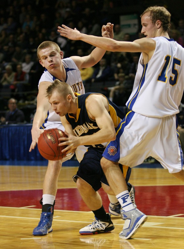 Medomak Panther's Zach Starr works to get past Falmouth's Andrew Thornton (left) and Grant Burfiend (right) during the Class B basketball state championship Friday, March 1, 2013, at the Cumberland County Civic Center in Portland.