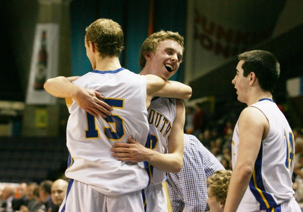 Falmouth High School's Thomas Wilberg (center) hugs Grant Burfiend (left) as the end of the Class B basketball state championship approaches Friday, March 1, 2013, at the Cumberland County Civic Center in Portland. Falmouth beat Medomak 62 to 39.