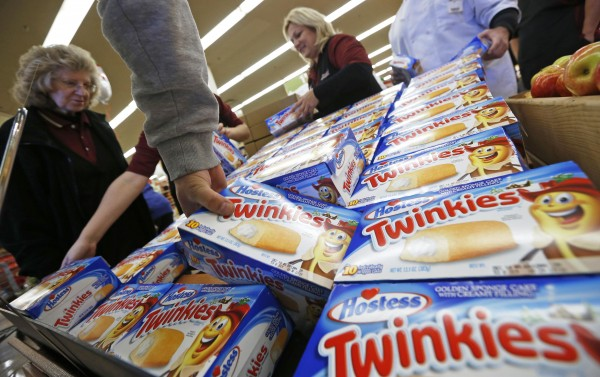 A bankruptcy court judge on Tuesday approved the sale of several iconic brands, including Twinkies, that had been owned by the failed Hostess Brands Inc. In this December 2012 file photo, customers grab boxes of Twinkies, as workers unpack what they believe is the last shipment of Twinkies at a Jewel-Osco grocery store in Chicago.