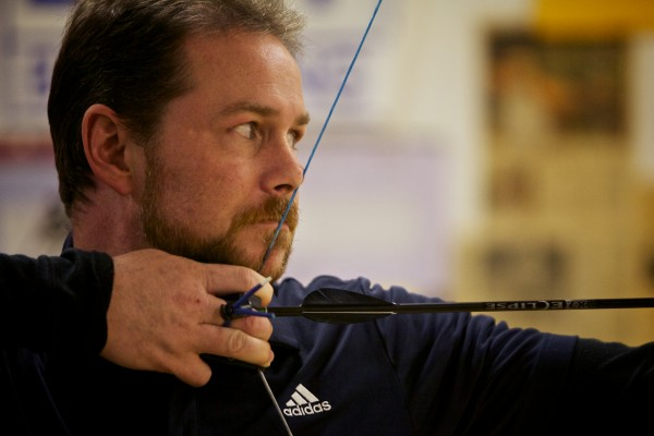 Archery coach Bill Duncanson aims an arrow at a target 20 yards away at Nicely Equipped Archery in Gorham.