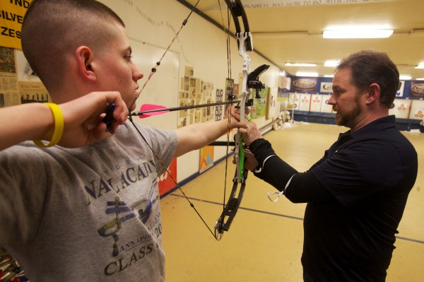 Coach Bill Duncanson works with Hayden Eilinger, 15, at an open shoot night at Nicely Equipped Archery in Gorham. Eilinger is preparing to compete at the U S National Indoor Championships in Virginia later this month.