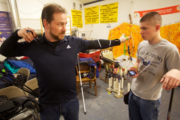 Coach Bill Duncanson talks with Hayden Eilinger, 15, at an open shoot night at Nicely Equipped Archery in Gorham. Eilinger is preparing to compete at the U S National Indoor Championships in Virginia later this month.