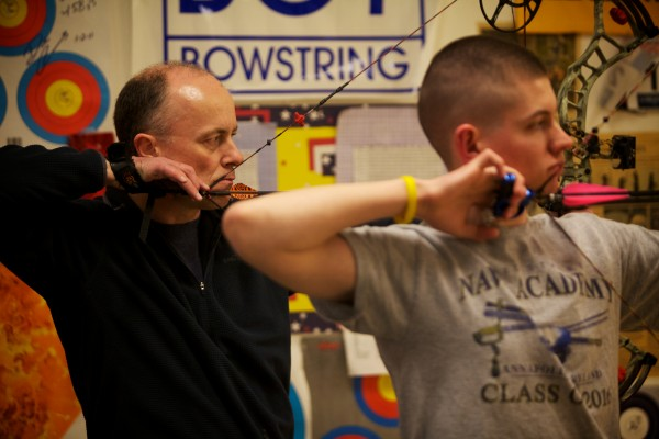 Rick Hilton (left) and Hayden Eilinger prepare to loose their arrows at Nicely Equipped Archery in Gorham.