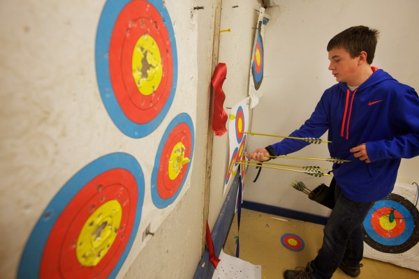 Josh Hilton, 12, retrieves his arrows on an open shoot night at Nicely Equipped Archery in Gorham.