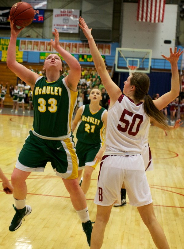 Victoria Lux (left) of Catherine McAuley High School goes to the hoop while guarded by Bangor High School's Cordelia Stewart Saturday in the Maine Class A Championship game at the Augusta Civic Center.