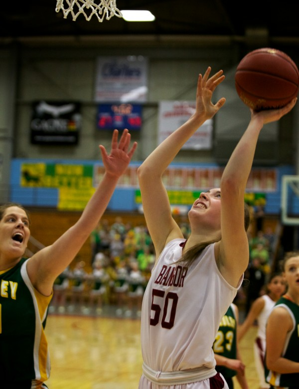 Bangor High School sophomore forward Cordelia Stewart shoots while guarded by Catherine McAuley High School's Molly E. Mack Saturday in the Maine Class A Championship game at the Augusta Civic Center.