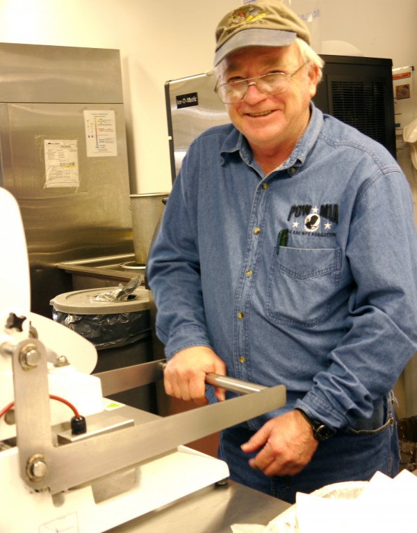 ohn Eckert from Augusta mans his station with a smile, heat sealing Meals on Wheels lunches at Spectrum Generations Cohen Center in Hallowell.