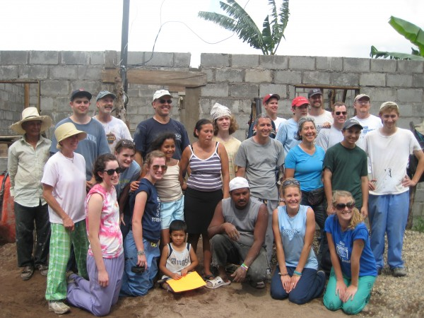 Members of the Assist-JC Mission Team and a grateful family pose in front of a house under construction in Honduras.