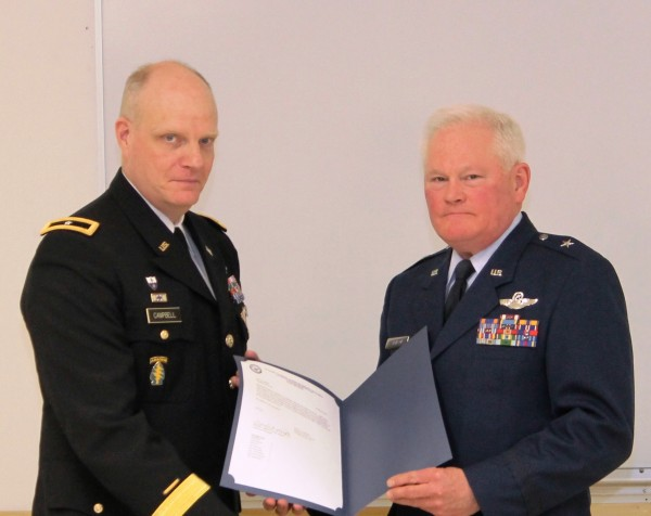 The adjutant general of Maine, Brig. Gen. James D. Campbell (left), congratulates Brig. Gen. Stephen M. Atkinson during his retirement ceremony held at the Augusta Armory.
