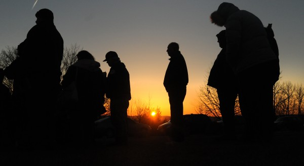 People stand listening to the church service held at the Thomas Hill Standpipe as the sun peaks over the horizon. The Columbia Street Baptist Church and members of other area Baptist churches participated in the service Easter Sunday morning.