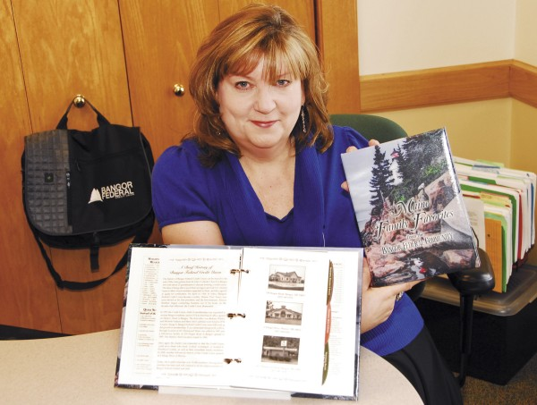 Evangeline Hussey, assistant to the CEO at Bangor Federal Credit Union, shows off the new cookbook.