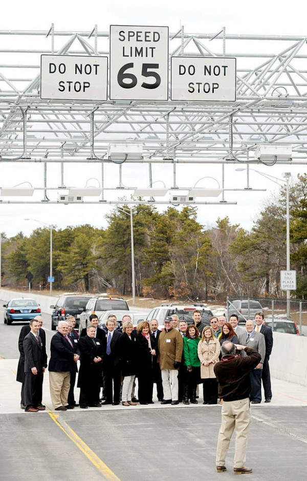Invited guests, including Maine Turnpike Authority board members, legislators, local officials, contractors and MTA Executive Director Peter Mills pose for photographer Kurt Brown of Westbrook at the new high-speed E-ZPass lanes in New Gloucester on Monday.