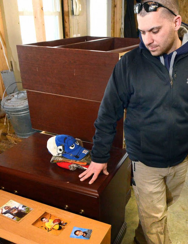 Adam Capponi looks at photos of his nephew Nathan at the home of his brother Kevin, who is still in shock after accidentally running over his son Wednesday morning.