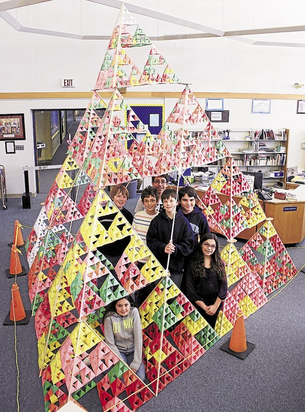 "Students enrolled at the James F. Doughty School in Bangor recently constructed a Stage 6 tetrahedron containing 4,096 individual tetrahedrons. The project originated with the book ""All of the Above,"" in which author Shelly Pearsall tells the story of four inner-city students who set a goal of building the largest tetrahedron in the world. While reading the book, Doughty School students decided to build a large tetrahedron; the completed tetrahedron involved more than 400 people, including students and teachers. Among the Doughty School students participating in the project were (kneeling) Elizabeth Remington and (standing, from left) Kyle Hylan-Corcoran, David Rubin, Gage Noyes, Noah Murphy, Joe Montemurro, and Hannah McCarthy."
