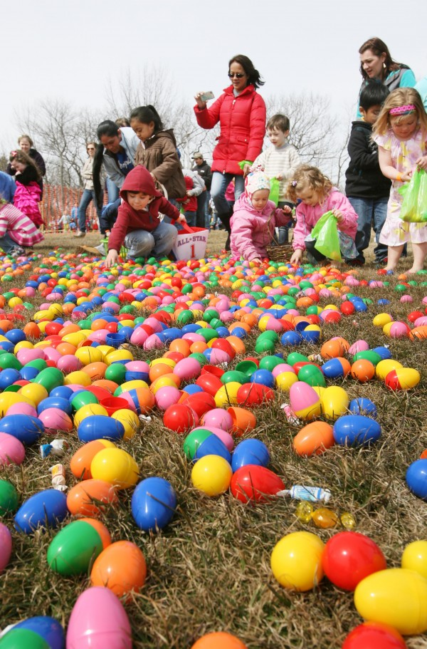 Children pick up candy-filled plastic Easter eggs that were dropped from a helicopter Sunday, March 31, 2013 as part of the Next level Church 2013 Helicopter Egg Drop in Portland, Maine.