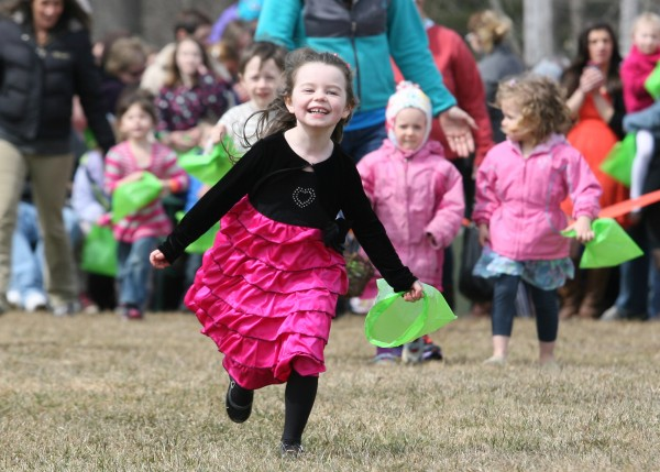An unidentified girl runs to pick up candy-filled plastic Easter eggs that were dropped from a helicopter Sunday, March 31, 2013 as part of the Next level Church 2013 Helicopter Egg Drop in Portland, Maine.