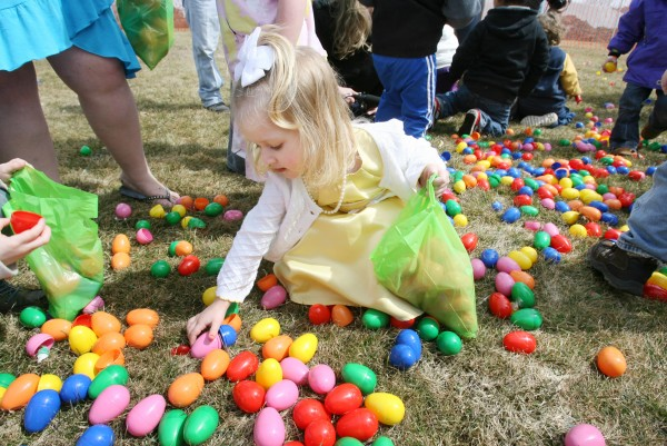 Emily Scellin, 3, picks up candy-filled plastic Easter eggs that were dropped from a helicopter Sunday, March 31, 2013 as part of the Next level Church 2013 Helicopter Egg Drop in Portland, Maine.