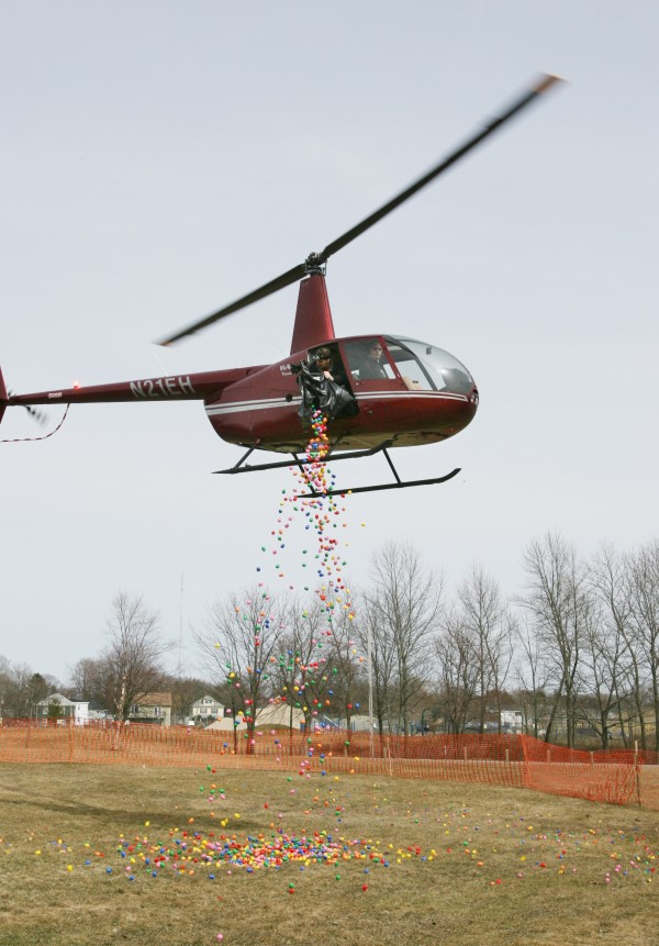 A unidentified man drops candy-filled plastic Easter eggs  from a helicopter Sunday, March 31, 2013 as part of the Next level Church 2013 Helicopter Egg Drop in Portland, Maine.