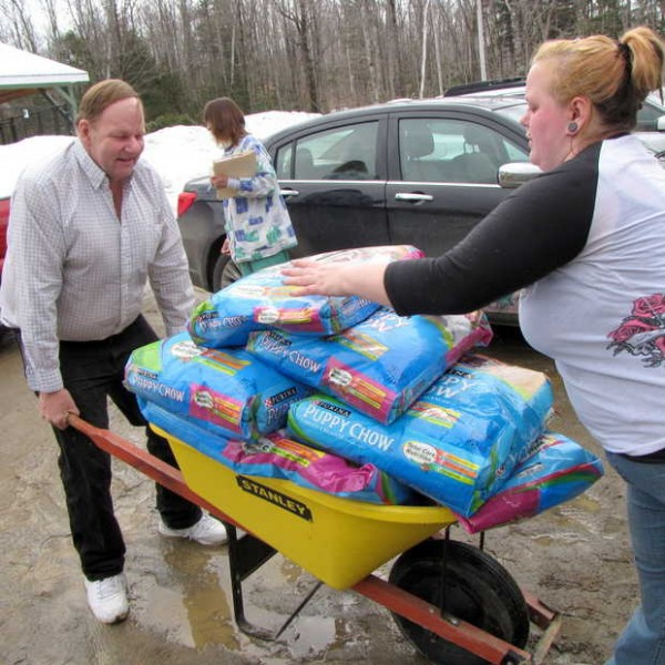 Franklin County Animal Shelter volunteers Dwayne Bulick and Danielle Towers help move bags of puppy chow in to storage Monday. People have donated items all weekend to help with the care of 75 dogs recently seized from a Wilton home.