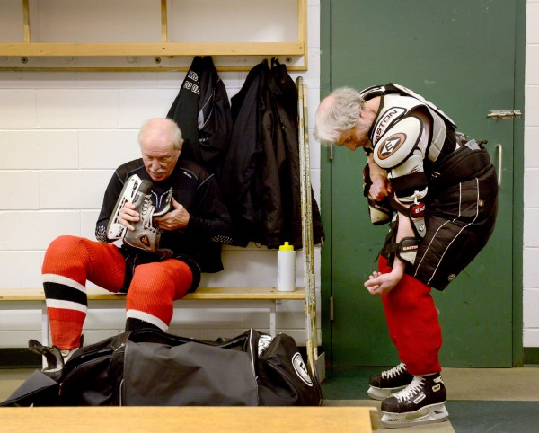 Clark Torrell, left, and Iver Mindel get dressed for a weekly hockey game at The Gardens Ice House in Laurel, Md., on Feb. 26, 2013. Every week, the group of men, mostly all over age 70, get together for a friendly game of hockey in the Gerihatrics league.