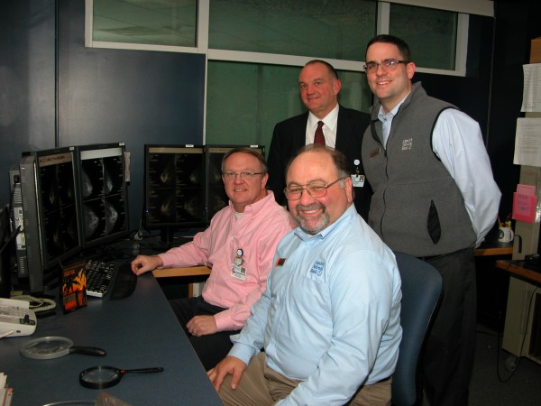 Camden National Bank is pleased to sponsor the 20th Annual Chefs' Gala.  Pictured reviewing firsthand the technology that has been made possible by the Chefs' Gala are seated L-R: Domenic Efter, Camden National Bank VP and Dr. Brian Ewy, Radiologist at MCMH.  Standing L-R:  Derek Hayes, Camden National Bank VP and MCMH CEO Charlie Therrien.  The proceeds from the 2013 Chefs' Gala will purchase Computer-Aided Detection (CAD) technology  as well as provide for mammogram scholarships at  the MCMH Breast Clinic.