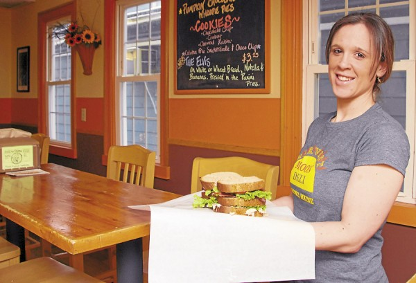 Manager Laurie Merrill displays a turkey club at the Harvest Moon Deli at 18 Mill St., Orono. The sandwich features oven roasted turley, bacon, green leaf lettuce, tomato, and mayonnaise on three layers of toasted bread. Photo taken on Friday, Marc1, 2013.