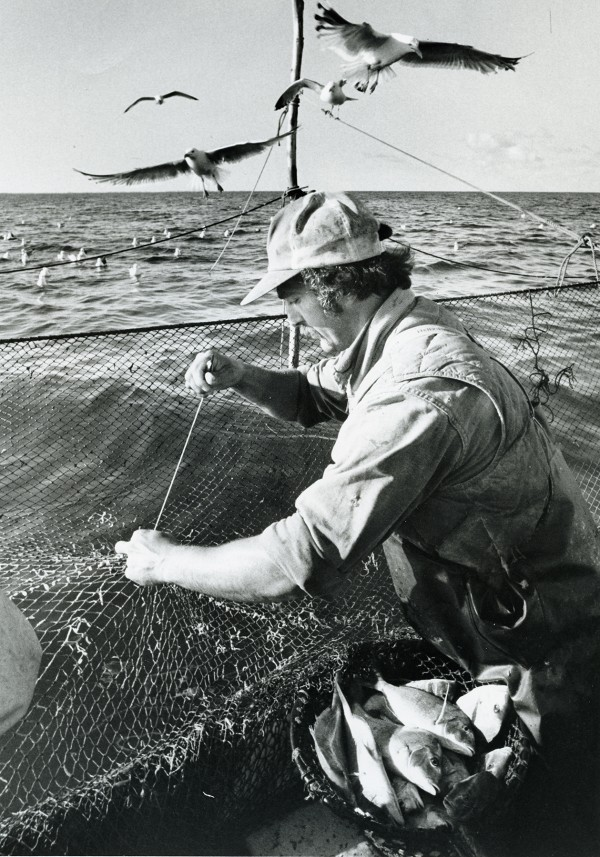 Mending nets is a never-ending chore if you're a fisherman! (Photo from the National Fisherman collection of the Penobscot Marine Museum.)