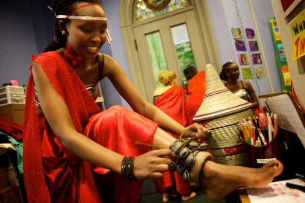 Dancer Diane Kankera of the Abeza B'Inganzo Troop ties bells to her ankles in the dressing room before performing at the fourth annual International Women's Day Fashion Show in Portland on Friday night. Kankera is originally from Rwanda.